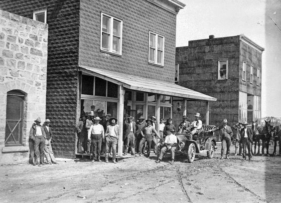 The men of the town of Ashland in Rosebud County turned out to have their photograph taken by L.A. Huffman circa 1910. There appear to be children peeking out the window of the building in the background.