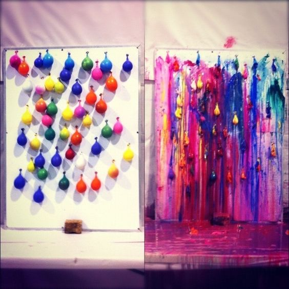 Tape or tack paint-filled balloons to a canvas and pop them using darts. Let the paint splatter wherever it goes and see how it turns out: