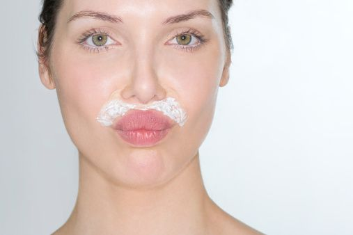 Woman bleaching facial hair