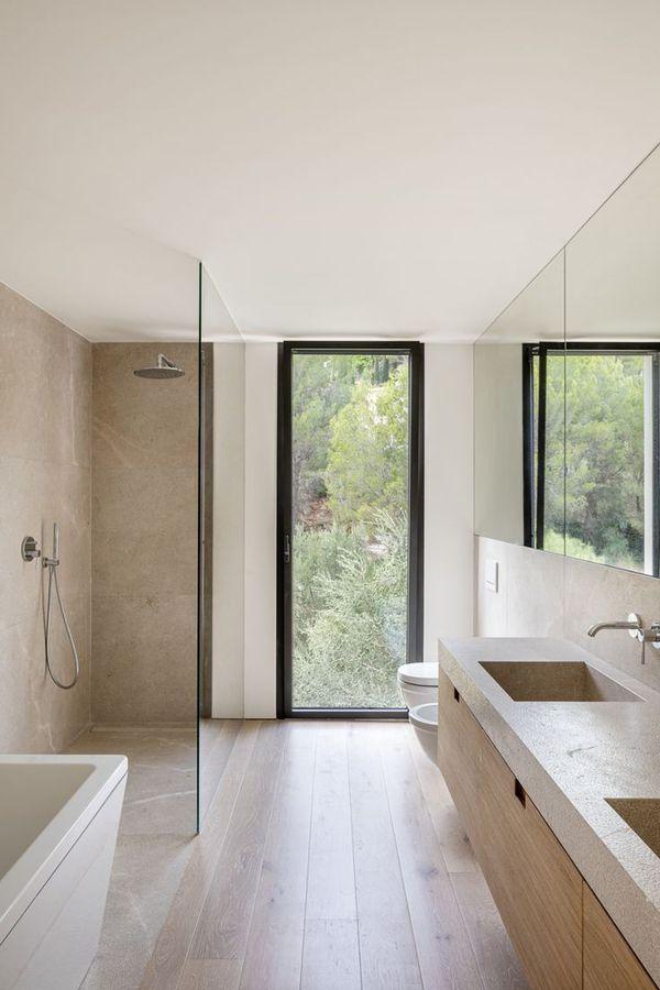 A simplistic bathroom with tan hies and a glass shower - Jorge Bibiloni Studio #interiordesign #homeideas #bathroom