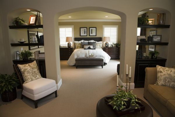 Triple arches bisect this master bedroom, segregating the sleeping and relaxing areas.