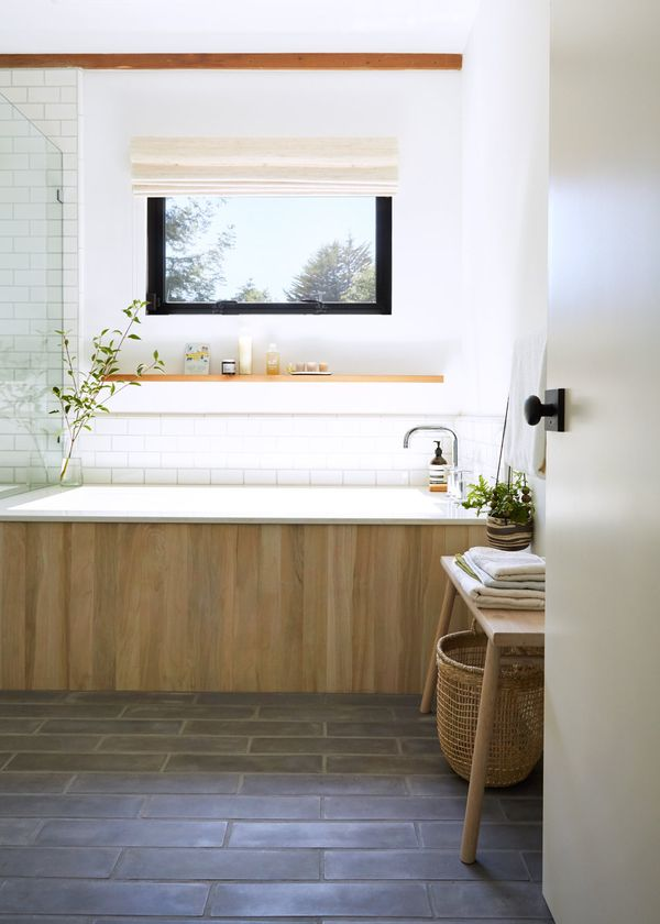 """The wood-grained ceramic exterior tub tile is from Vallelunga & Co. (VL-3006 Tabula Miele). """"It was a bit clunky in its original 6-inch width, so we trimmed it to 3 inches on site. The shower and tub trim tile is 3-by-6-inch Savoy Field Tile in Rice Paper from Ann Sacks."""