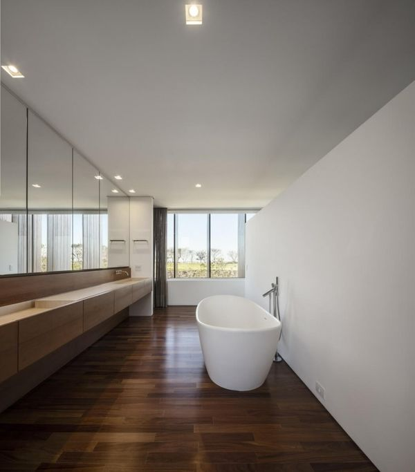 Gorgeous White Wall Paint Bathroom Design With Stunning Brown Wood Laminate Flooring And Enchanting Mirror