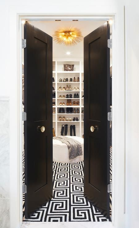 Black bi-fold doors fitted with large gold door knobs open to a walk-in closet filled with a a round white tufted ottoman placed atop a black and white Greek key rug leading to a wall of floor to ceiling built-in shoe and boot shelves illuminated by a brass sea urchin flush mount light.