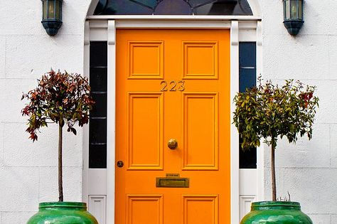 Bright citrus orange front door with white brick facade, bookended with emerald