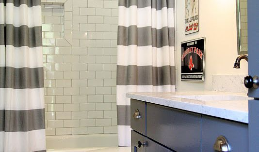 Love the striped shower curtains and blue cabinets for the boys' bathroom