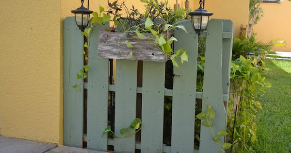 Paint an old wood pallet and use to hide trash cans or