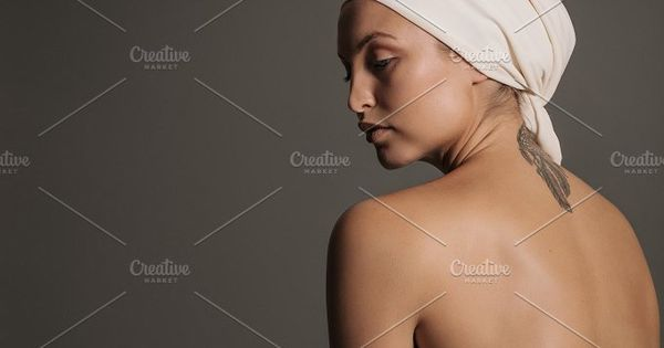 Studio shot of young woman with naked back against grey background. Beautiful nude woman with a scarf wrapped on her head.