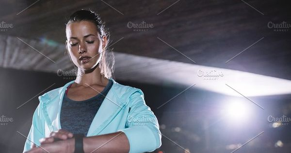 Urban runner checking fitness progress on her smart watch. Woman monitoring workout performance on her watch.