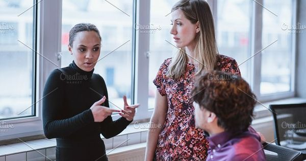 Young woman explaining business strategy to colleagues. Multiracial businesspeople discussing work in office.