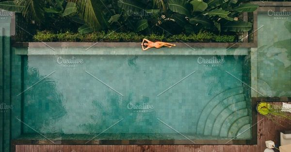 Aerial view of female model lying at the poolside. Young woman in bikini relaxing on the edge of the swimming pool of luxury resort.