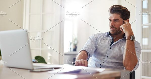 Shot of businessman sitting at table looking at laptop and thinking. Thoughtful businessman working at home office.