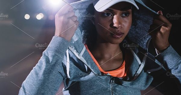 urban runner standing on the street at night. Young woman in sportswear standing outdoors