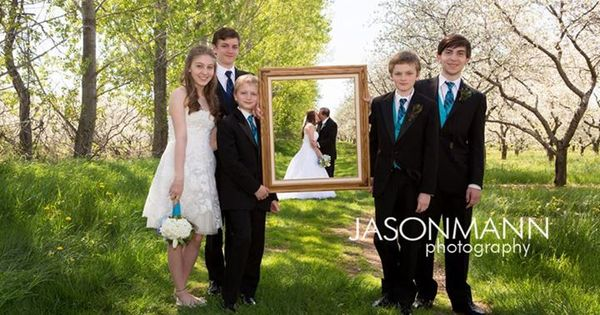 Groom And Bride S Children Hold A Frame Around The Kissing