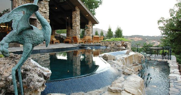 Freeform Vanishing Edge Pool With Tile And Boulders Open Air Patio With Stacked Stone Pillars
