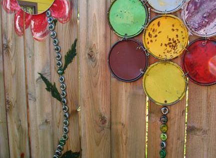 """Fence flowers made from paint can lids, bottle caps and mirrors."" -"