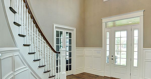 Two Story Foyer Wainscoting : Curved staircase in two story foyer with white wainscoting