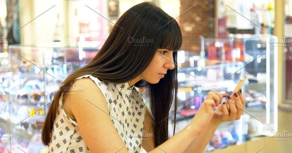 Young woman playing Pokemon GO indoor at shopping center, using smart phone. Girl play the popular smartphone game – catching pokemon in hypermarket mall