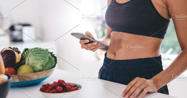Cropped shot of young woman using mobile phone in kitchen with fruits and vegetable on kitchen counter.