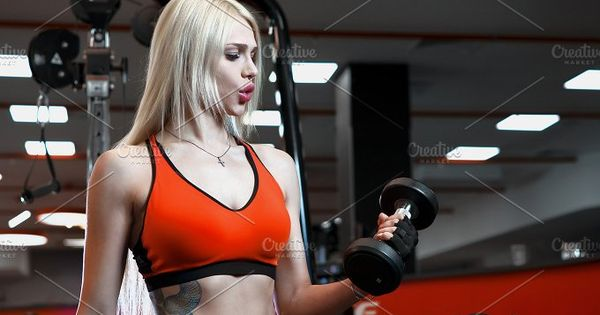 Portrait of a beautiful sexy woman dressed in sports clothes in the gym. Fitness female with muscular body ready wearing hand gloves for workout.