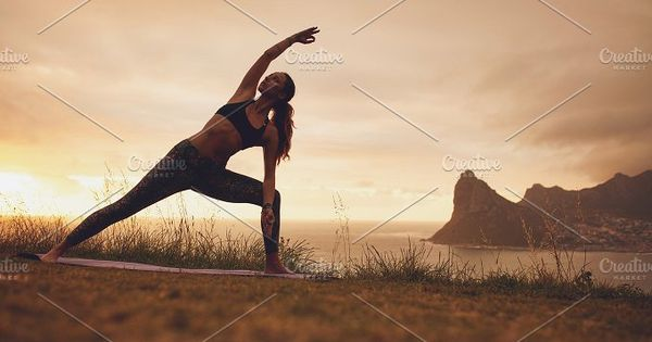 Full length shot of young woman practicing Utthita Parsvakonasana yoga asana. Healthy female exercising at sunset on the cliff.