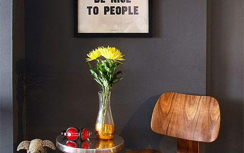 Charcoal grey walls, midcentury chair, 'work hard and be nice to people'