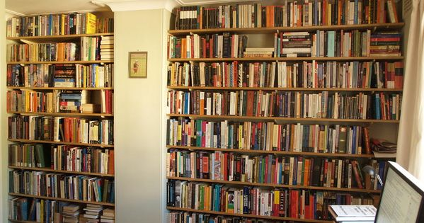 Ceiling High Wall Book Shelves With Bright Wooden Parions And Full Books Rack Plain Brown Carpet White Painted