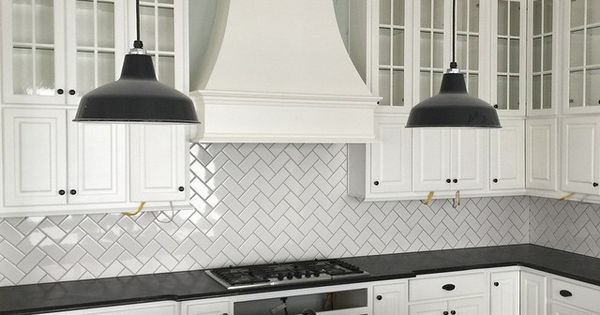 Classic subway tile laid with a herringbone pattern in one of our cottage homes in ...