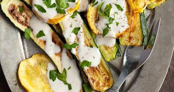 Grilled zucchini and summer squash are served with a cumin yogurt sauce