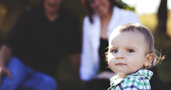 one year old boy sitting in front of his mom and dad
