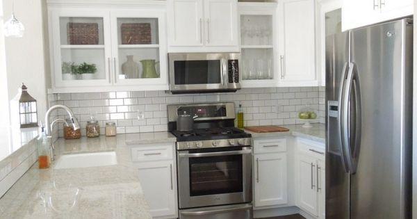 White kitchen. Dark floors. Stainless steel appliances. Microwave hood fan/hood vent over