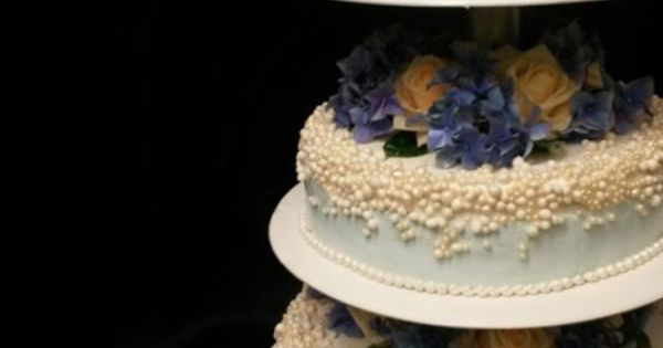 Hochzeitstorte mit perlenartiger Verziehrung und gelb-blauen Blumen ...