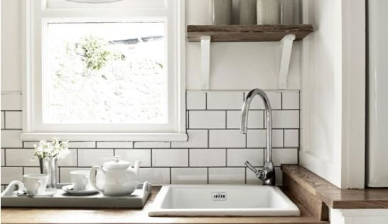 white subway tiles, dark grout, wood countertop, wonderful clock