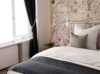 Use a vintage map or graphic wallpaper on a feature wall for Wallpaper for wall behind bed