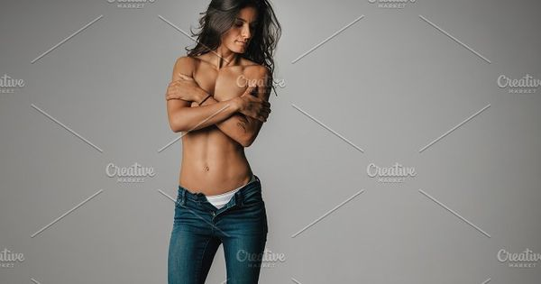Athletic woman with partially unbuttoned blue jeans and folded arms over bare chest. Includes copy space.