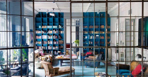 stunning blue built-in bookshelves, colorful living room area, glass steel doors between