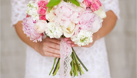 Pink And White Wedding Bouquet overflowing with peonies, roses and sweet peas. Wrapped up perfectly with a pink lace bow.