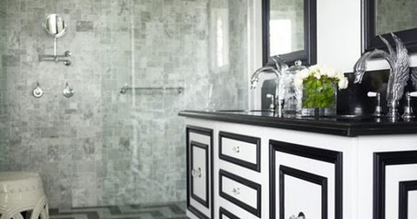Striking black and white bathroom with chevron marble tiled floor. Modern footed