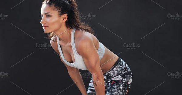 Shot of young fitness woman standing on black background. Muscular female model in sportswear.