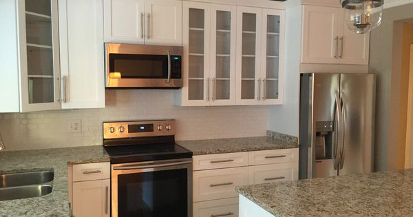 White shaker cabinets a light granite and glass doors for Windowless kitchen sink