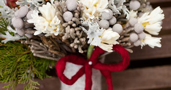 silver brunia, dusty miller, antique green hydrangea, pepper berry, paper whites, and white hyacinthus. The bouquet was wrapped in grey wool, and red wool ribbon
