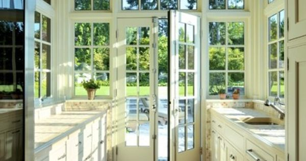 Greenhouse kitchen with an abundance of natural light. Warm wooden floors.