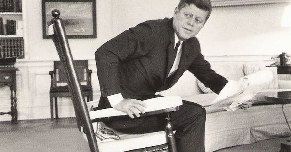 ... John F. Kennedy rises from his favorite rocking chair in the Oval