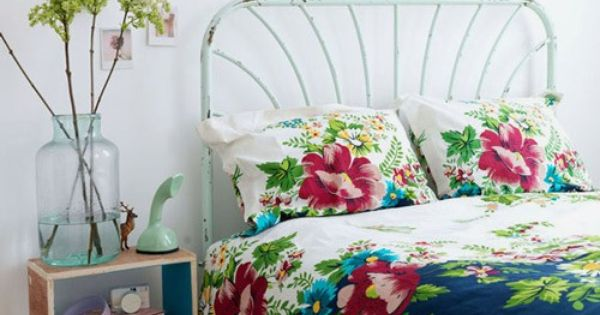 floral bedding. metal bed frame. stacked crates for bedside table. knick-knacks.