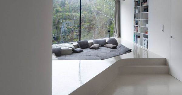 This comfy lounge area has been sunken into a built up for Bed built into floor