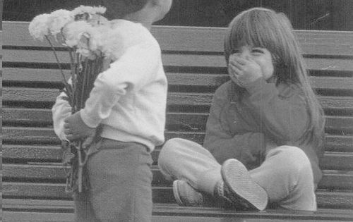 black and white photo of little boy giving little girl flowers