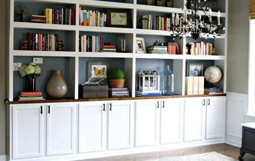 DIY built in bookcases using upper kitchen cabinets for base....along the wall