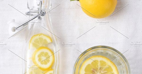 Top view of a glass of lemon water next to a swing bottle and whole piece of fruit.