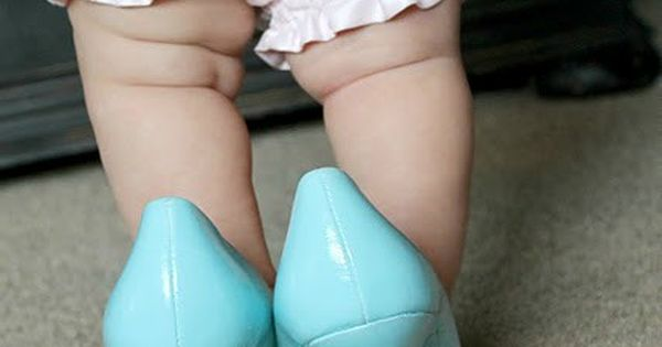 Baby girl in moms wedding shoes