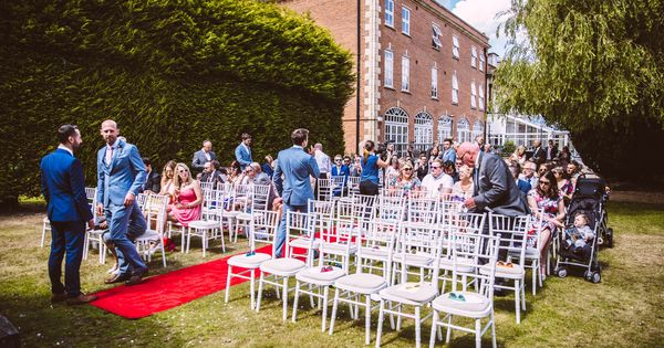 White chiavari chairs supplied by pollen4hire for an outside ceremony